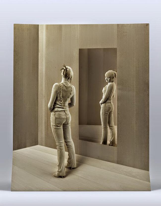 Eine junge Frau schaut sich im Spiegel an